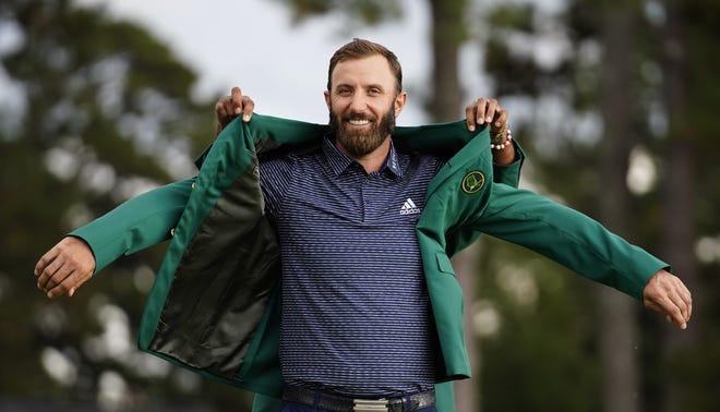 Dustin Johnson slips on the green jacket for his Masters win last November.