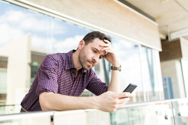 A man looking upset while reading something on his phone.
