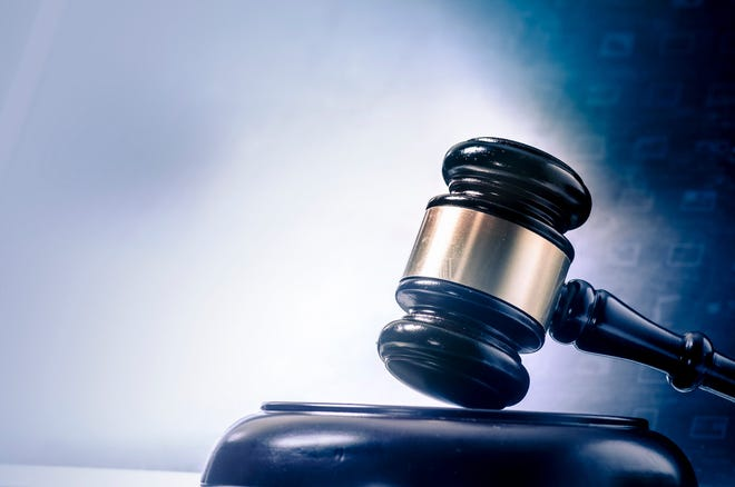 A judge's gavel resting on a wooden stand with barely visible numbers in the background.