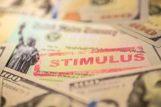 """A photo of the economic stimulus check from the U.S. Treasury, with the word """"STIMULUS"""" boldly stamped across it. The check is surrounded by $100 bills."""