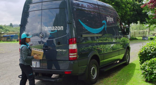 An Amazon delivery worker carries a package next to an Amazon delivery truck