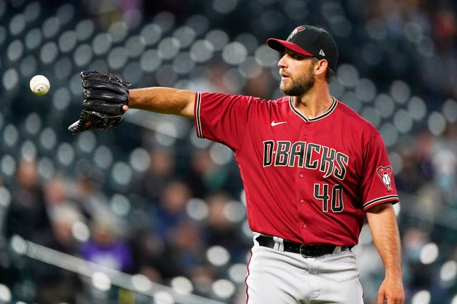 Arizona Diamondbacks starting pitcher Madison Bumgarner gets a new ball while arguing a call after issuing a walk to Colorado Rockies' Ryan McMahon during the third inning of a baseball game Wednesday, April 7, 2021, in Denver. (AP Photo/David Zalubowski)