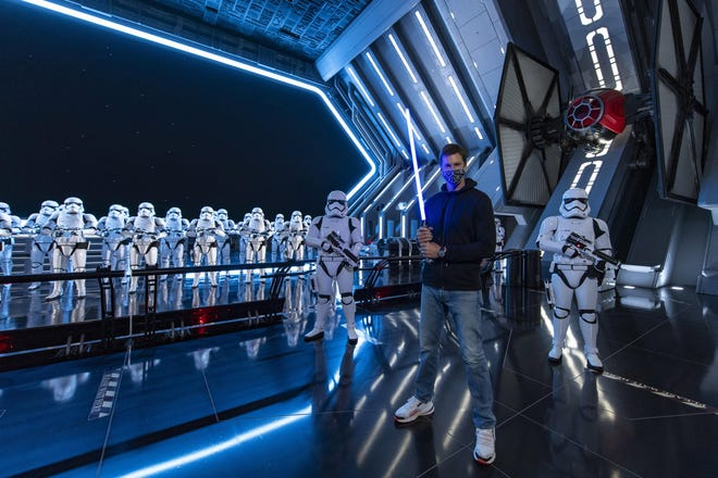 NFL star Tom Brady visits Star Wars: Galaxy's Edge inside Disney's Hollywood Studios at Walt Disney World Resort in Lake Buena Vista, Fla., on Monday. A mask-wearing Brady visited the Star Wars-themed section of Walt Disney World with his family and friends, two months after he led the Tampa Bay Buccaneers to a Super Bowl win against the Kansas City Chiefs.