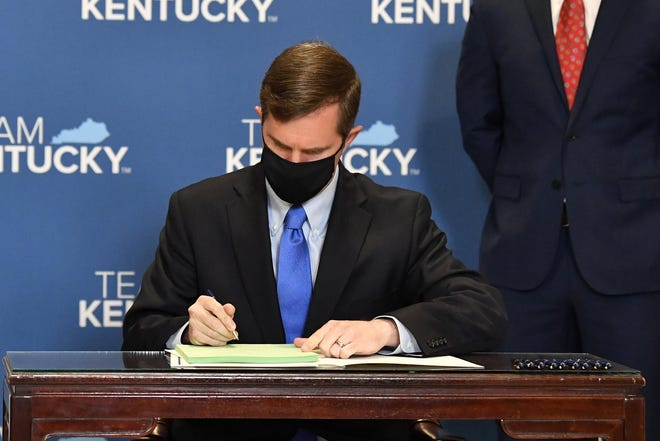 Kentucky Gov. Andy Beshear signs a bill related to the American Rescue Plan Act at the Kentucky State Capitol in Frankfort on Wednesday.