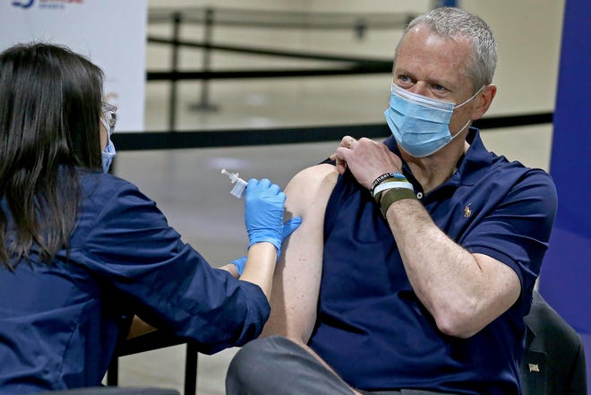 Massachusetts Gov. Charlie Baker, 64, receives a Pfizer COVID-19 vaccine at the Hynes Convention Center on Tuesday in Boston.