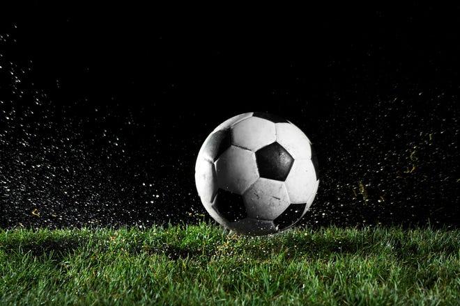 A soccer ball on wet grass at night.
