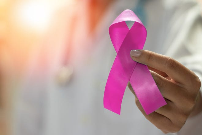 Physician holding a pink breast cancer awareness ribbon