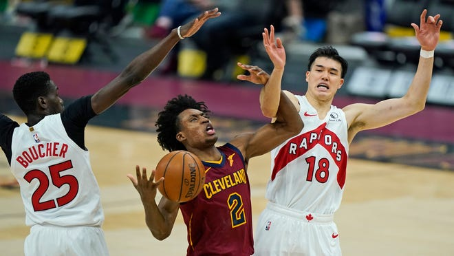 Cleveland Cavaliers' Collin Sexton (2) drives between Toronto Raptors' Yuta Watanabe (18) and Chris Boucher (25) in the first half of an NBA basketball game, Saturday, April 10, 2021, in Cleveland. [Tony Dejak/Associated Press]