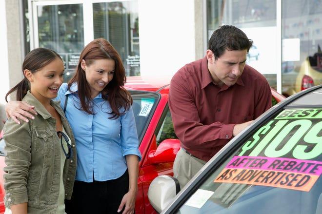 رجل وامرأة وشاب ينظرون إلى سيارة في ساحة انتظار سيارات مستعملة.