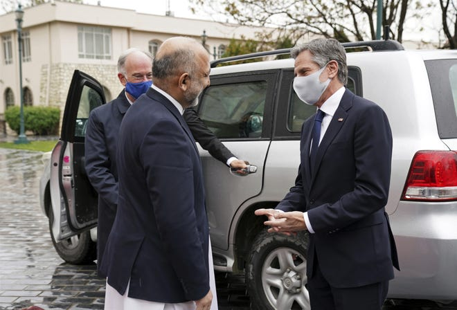U.S. Secretary of State Antony Blinken, right, talks with Afghanistan's Foreign Minister Mohammad Haneef Atmar Thursday outside the presidential palace in Kabul, Afghanistan. Blinken made an unannounced visit to Afghanistan on Thursday to sell Afghan leaders and a wary public on President Joe Biden's decision to withdraw all American troops from the country and end America's longest-running war.