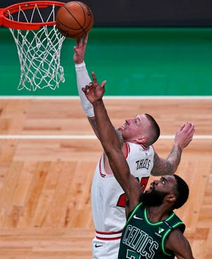 Chicago Bulls center Daniel Theis, left, tries to tip in a rebound against Boston Celtics guard Jaylen Brown, right, during the first half of a game on Monday, April 19, 2021, in Boston.