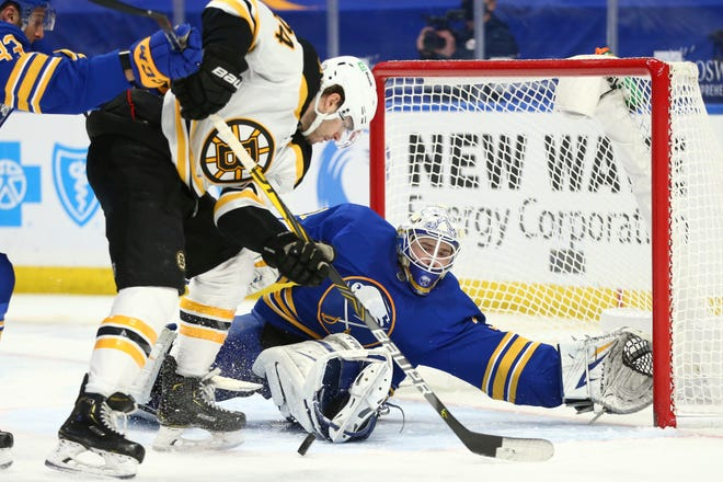 Buffalo Sabres goalie Dustin Tokarski (31) stops Boston Bruins forward Jake DeBrusk (74) during the second period of an NHL hockey game, Tuesday, April 20, 2021, in Buffalo, N.Y. (AP Photo/Jeffrey T. Barnes)