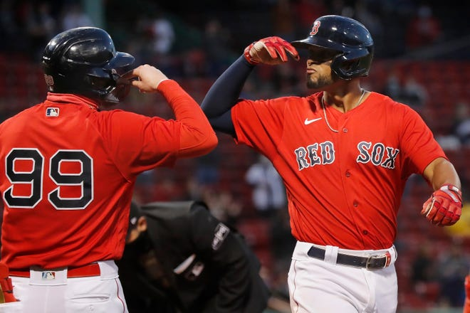 Boston Red Sox's Xander Bogaerts celebrates his two-run home run that also drove in Alex Verdugo (99) during the first inning of a baseball game against the Seattle Mariners, Friday, April 23, 2021, in Boston. (AP Photo/Michael Dwyer)