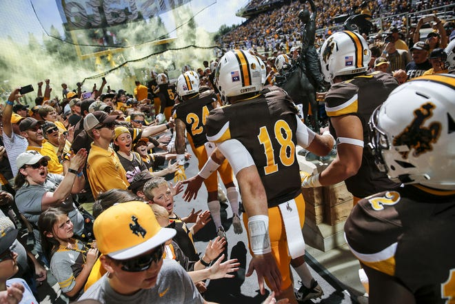 Fans greet the Wyoming Cowboys as they take the field for their game against Wofford at War Memorial Stadium Saturday afternoon, Sept. 15, 2018.