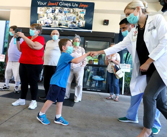 Parker Kay, 5, fist bumps Aubrey Hall, an acute care nurse practitioner who was working with Parker's mom, Kristin. Kristin Kay is recovering from the long-term effects of COVID-19 and was leaving North Florida Regional Medical Center in Gainesville on April 19, after being hospitalized since January. She was going to another facility to continue physical and occupational therapy for weeks in the final stretch of her recovery from COVID-19.