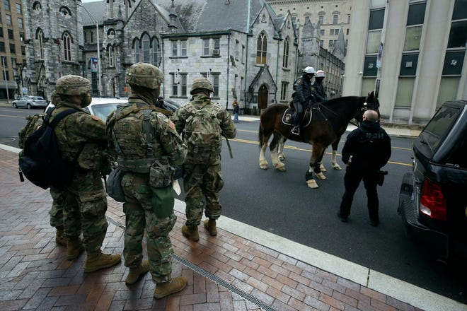 Pennsylvania State Police on horseback pass a group of National Guard in front of the Pennsylvania State Capitol Sunday Jan. 17, 2021 in Harrisburg, Pa.