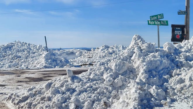 The piles of snow nearly bury road signs at Maple Valley Road and Suder Road, Summit Township, on Thursday. Karamie Johnson, of Meyersdale, said snow plows were clearing more room for vehicles on the road when she took this photo Thursday afternoon.