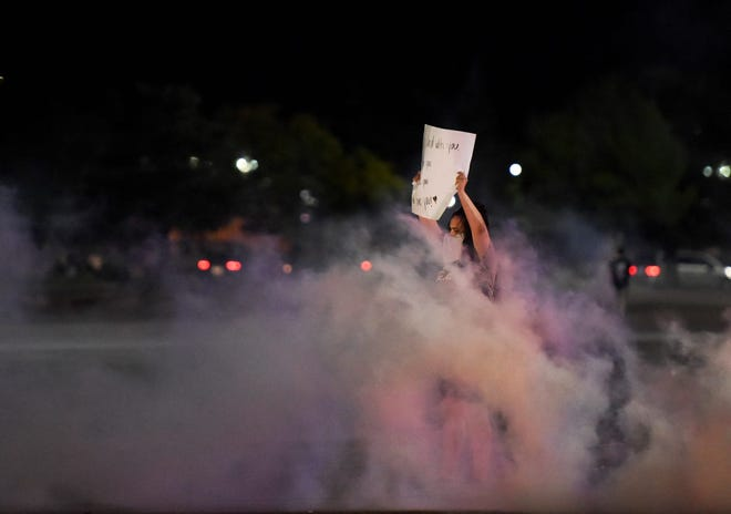 A lone protestor holds a sign in a cloud of tear gas on Sunday, May 31, 2020 in Sioux Falls, S.D.
