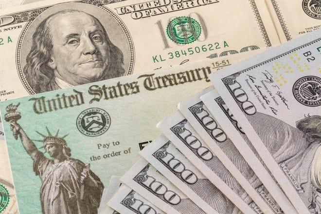 Stack of 100 dollar bills next to a coronavirus stimulus check.