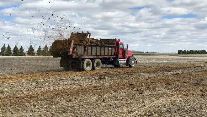 North Dakota State University spreads manure at the Carrington Research Extension Center.