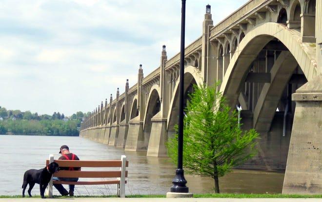 A senior citizen rests with his dog near a bridge in Columbia, Pennsylvania.
