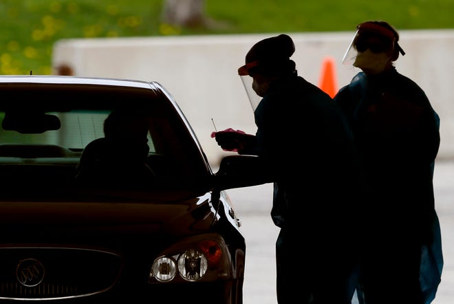 Medical workers test a local resident at a drive-thru coronavirus testing site in Waterloo, Iowa, on May 1, 2020.