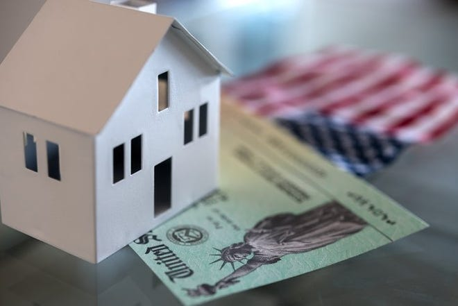 A white cardboard house sits on top of a stimulus check and a small American flag.