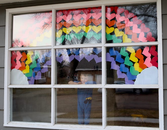 """Jackson Davis stands under the rainbow of hearts he and his family created on the window of their home. Many people have taken up this cheerful decoration to keep positivity during times when most people are staying at home. The trend is known online as """"A World of Hearts,"""" and thousands of posts on social media show colorful hearts in windows, drawn on the sidewalk in chalk and many other creative designs and messages. Have you participated in #aworldofhearts? Send us your photos on Facebook or email them to lbutterbrodt@thepublicopinion.com."""
