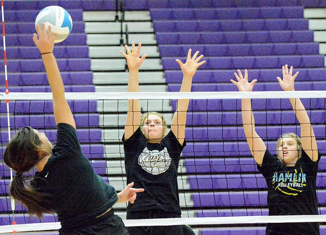Hamlin's McKenna Prouty (left) hits the ball against blockers Gracelyn Leiseth and Ally Abraham (right) during the Chargers' practice in preparation for the state Class A volleyball tournament in the Civic Arena. The tourney runs Thursday through Saturday.