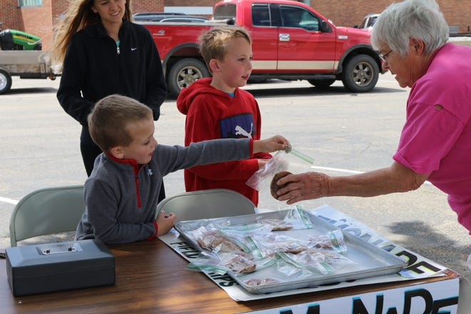 Bennett Roby, age 5, hands Darlene Hanten a cookie during a Kids On Target fundraiser with 9-year-old Jonah Raml (center) Wednesday.