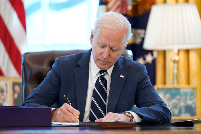 President Joe Biden signs the American Rescue Plan, a coronavirus relief package, Thursday in the Oval Office of the White House in Washington.