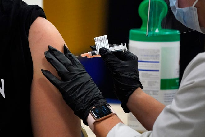 A student receives her first dose of the Moderna COVID-19 vaccine during a vaccination clinic hosted by the University of Pittsburgh and the Allegheny County Health Department at the Petersen Events Center, in Pittsburgh, Thursday, Jan. 28, 2021.