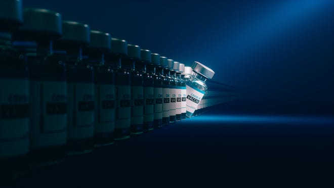 COVID-19 vaccine vials in a row with a light shining on one vial tipping over.