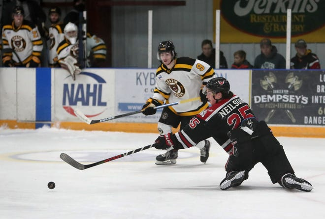 Cade Neilson, of the Aberdeen Wings, right, reaches for the puck from his knees as Nick Catalano, of the Austin Bruins, back center, looks on during a game at the Odde Ice Center. American News file photos