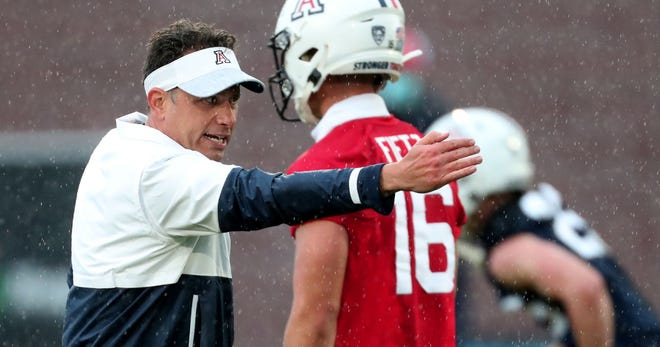 First-year head coach Jedd Fisch works a bit with the quarterbacks on the first day of spring practice for the University of Arizona. Fisch has taken over a program that has lost 12 straight games.