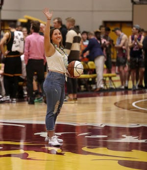 Northern State University's Brianna Kusler waves to the crowd in Wachs Arena after receiving a ball in honor of achieving the 1,000 point mark in her career.