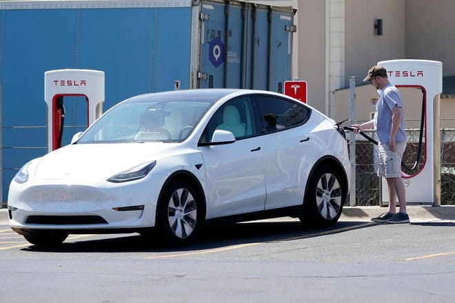 A Tesla owner charges his vehicle at a charging station in Topeka, Kan., on April 5.