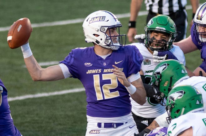 James Madison quarterback Cole Johnson (12) looks for an open receiver under pressure from the North Dakota defense during the first half of a quarterfinal game in the NCAA FCS football playoffs in Harrisonburg, Va., Sunday, May 2, 2021. (Daniel Lin/Daily News-Record via AP)