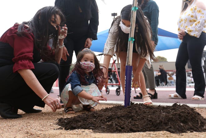 Lisa Soria, from left, Violet Franco and Leah Najera help plant a tree in memory of Leobardo Soria and his wife, Rosie Soria, on April 27 at Carroll T. Welch Elementary in Horizon City, Texas, where Leobardo was a security guard. Leobardo and Rosie died of COVID-19. The Clint Independent School District honored three employees who passed away during the pandemic in memorial services that week.