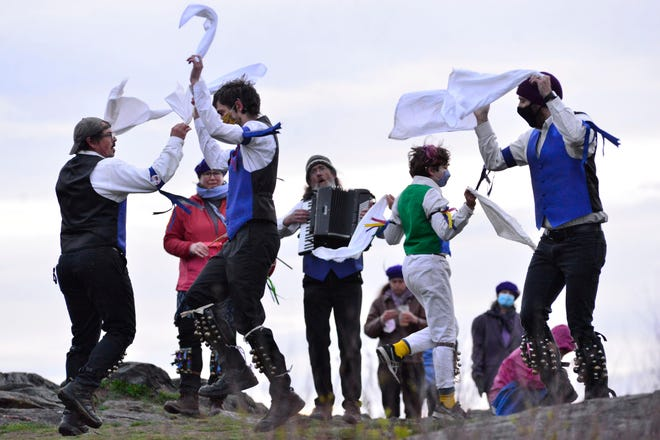 A small group of people welcomes the rising of the first sunrise in May with an impromptu Morris dance on top of Putney Mountain on Saturday in Putney, Vt. Gov. Phil Scott loosened COVID-19-related restrictions on outdoor gatherings the day prior.