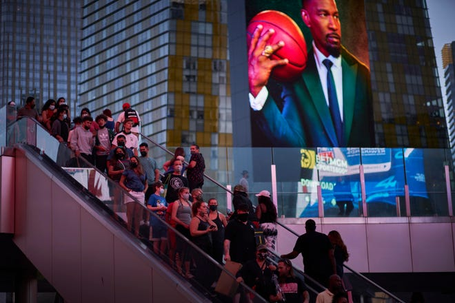 People ride an escalator along the Las Vegas Strip on Saturday. Las Vegas is bouncing back to pre-pandemic levels, with increases in airport passengers and tourism.