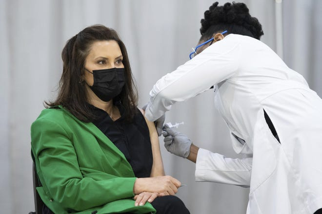 Michigan Gov. Gretchen Whitmer receives her second dose of Pfizer's COVID-19 vaccine from Dr. Joneigh Khaldun at DeVos Place on Thursday in Grand Rapids, Mich.
