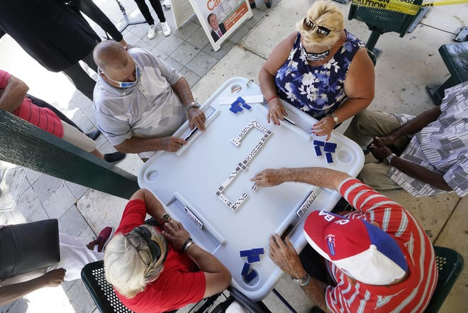 People play dominoes at Maximo Gomez Park, also known as Domino Park, in the Little Havana neighborhood of Miami, which reopened Monday after it was closed last year due to the COVID-19 pandemic.