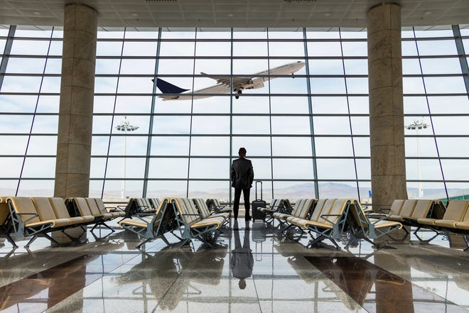 Man in airport looking at a departing plane.