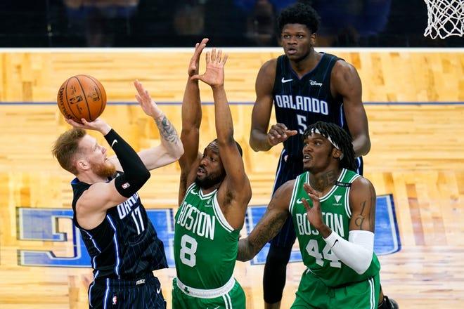 Orlando Magic forward Ignas Brazdeikis (17) takes a shot over Boston Celtics guard Kemba Walker (8) and center Robert Williams (44) as Magic center Mo Bamba (5) looks on during the first half of an NBA basketball game, Wednesday, May 5, 2021, in Orlando, Fla. (AP Photo/John Raoux)