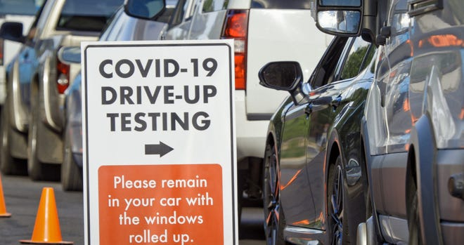 A COVID testing drive up location with cars lined up and an orange and white sign with an arrow pointing to the line.