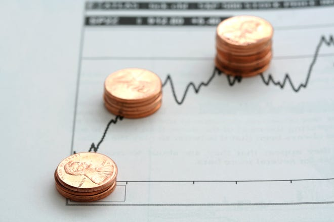 Three stacks of pennies on top of a stock chart
