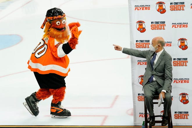 Gov. Tom Wolf gestures at Philadelphia Flyers mascot Gritty on Monday in Philadelphia during a news conference encouraging people to get a COVID-19 vaccine.