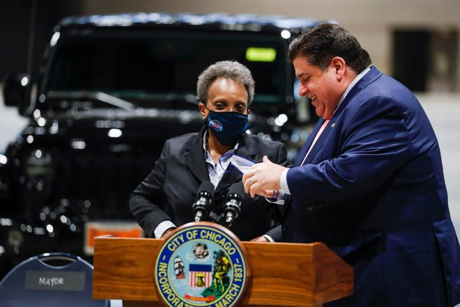 Illinois Gov. J.B. Pritzker and Chicago Mayor Lori Lightfoot talk after a news conference about the city's reopening efforts Tuesday at McCormick Place, where the Chicago Auto Show is slated to be held this July.