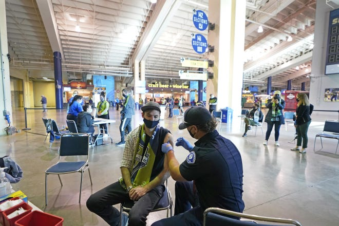 Austin Kennedy, left, a Seattle Sounders season ticketholder, gets the Johnson & Johnson COVID-19 vaccine Sunday at a clinic in a concourse at Lumen Field in Seattle, prior to an MLS soccer match between the Sounders and the Los Angeles Galaxy.